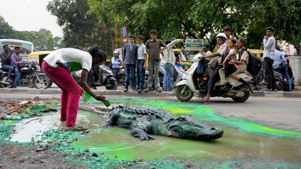 The artists at work, adding the finishing touches to his crocodile.