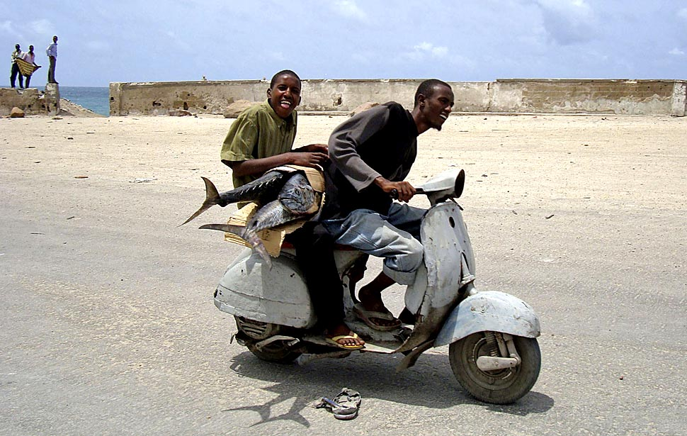 A Somali boy carries a sword fish as he rides on a motorcycle taxi in southern Mogadishu. (REUTERS/Feisal Omar)